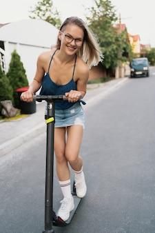 Młoda piękna dziewczyna jedzie na skuterze elektrycznym latem na ulicy