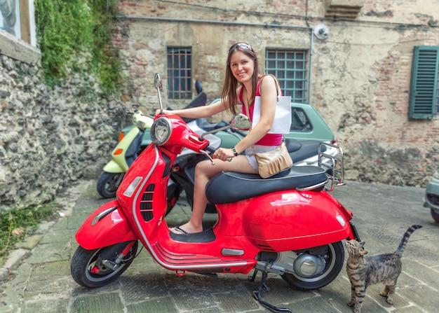 Młoda piękna dziewczyna jeździ czerwonym motocyklem vespa ulicami rzymu we włoszech.
