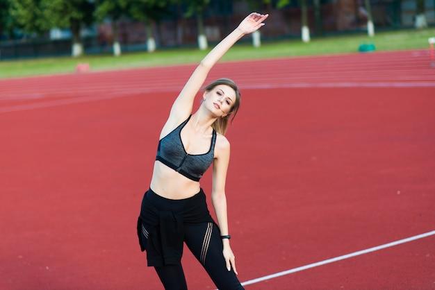 Młoda piękna dziewczyna lekkoatletka w odzieży sportowej trenuje i biegnie, rozciągając się na stadionie