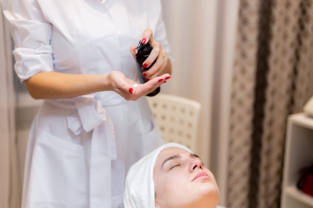 Młoda piękna dziewczyna leży na stole kosmetyczki i otrzymuje zabiegi, lekki masaż twarzy na olejku.
