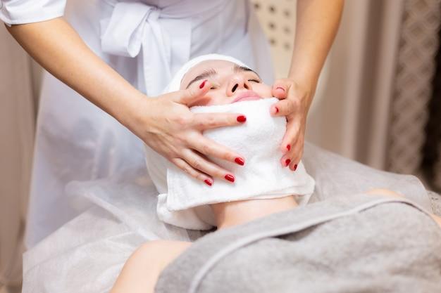 Młoda piękna dziewczyna leży na stole kosmetyczki i otrzymuje zabiegi, lekki masaż twarzy.