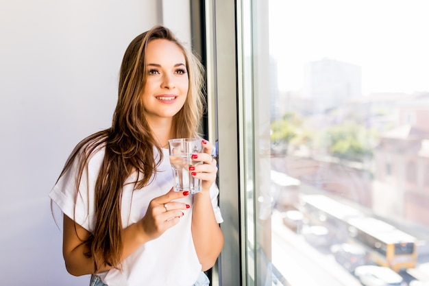 Młoda piękna dziewczyna lub kobieta ze szklanką wody w pobliżu okna w białej koszuli i szarej szacie