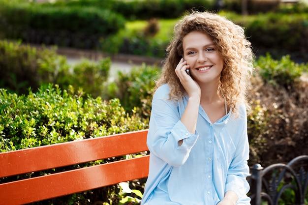 Młoda piękna dziewczyna mówi na telefon, siedząc na ławce.