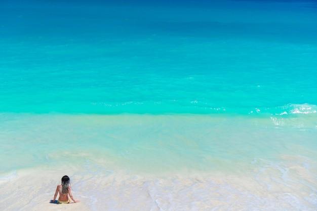 Młoda piękna dziewczyna na plaży przy płytkim tropikalnym wodnym odgórnym widokiem