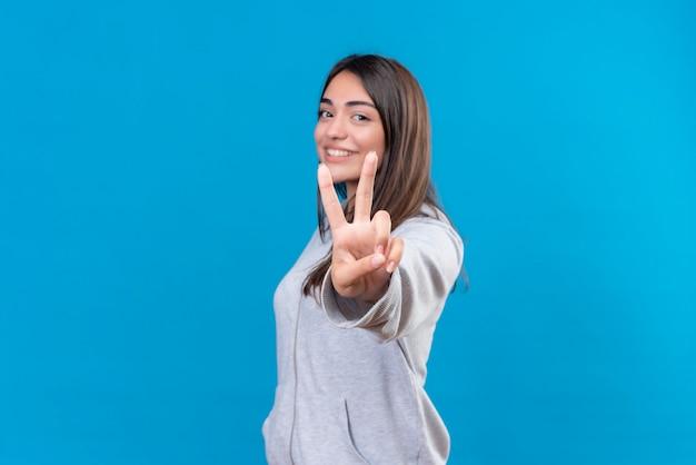 Młoda piękna dziewczyna na szaro patrząc na kamery z uśmiechem na twarzy czyniąc gest pokoju stojąc na niebieskim tle
