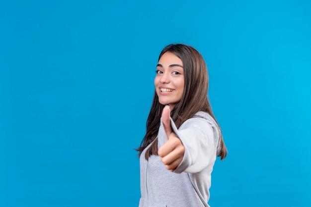 Młoda piękna dziewczyna na szaro w bluza z kapturem, patrząc na kamery z uśmiechem na twarzy, robiąc jak gest do kamery stojącej na niebieskim tle