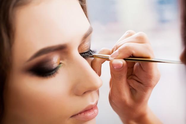 Młoda, piękna dziewczyna nakłada makijaż w salonie piękności
