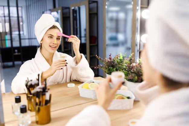 Młoda piękna dziewczyna nakłada złotą maskę na twarz przed lustrem