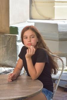 Młoda piękna dziewczyna nastolatka jedzenie cukierków kokosowych na tarasie