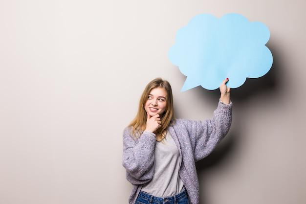 Młoda piękna dziewczyna nastolatka trzyma niebieski bańki tekstu, odizolowane