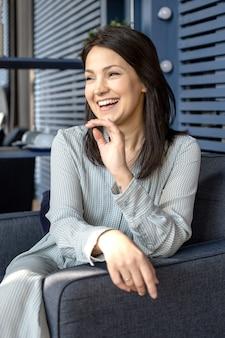 Młoda piękna dziewczyna o azjatyckim wyglądzie uśmiecha się i siedzi na krześle
