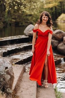 Młoda piękna dziewczyna o długich brązowych włosach w długiej czerwonej sukience schodzi po schodach w pobliżu jeziora,