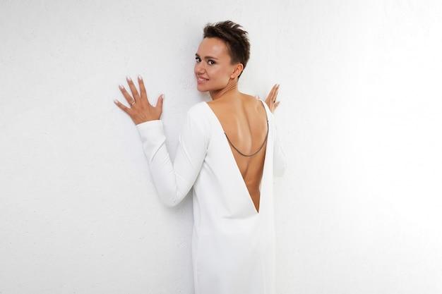 Młoda piękna dziewczyna o krótkich ciemnych włosach, w długiej białej sukni z otwartymi plecami, stoi z powrotem do aparatu