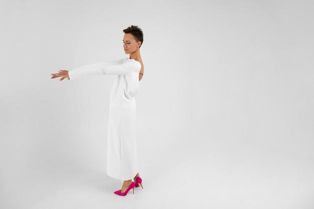 Młoda piękna dziewczyna o krótkich ciemnych włosach, w długiej białej sukni z otwartymi plecami, stoi z powrotem przed kamerą i wygląda na bok