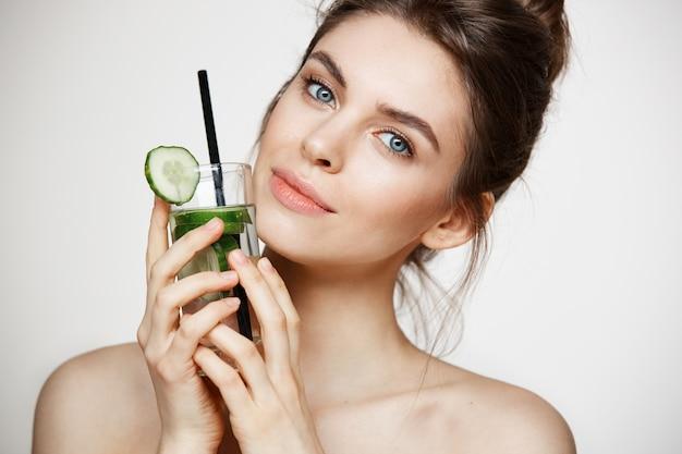 Młoda piękna dziewczyna ono uśmiecha się z perfect czystą skórą patrzejący kamerę trzyma szkło woda z ogórków plasterkami nad białym tłem. zdrowe odżywianie.