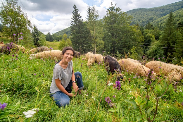 Młoda piękna dziewczyna pasterz pasie stado owiec w zielonym polu.