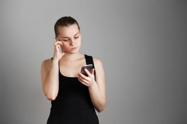 Młoda piękna dziewczyna patrzy na telefon i myśli, zaskoczony. nad szarą ścianą. skopiuj miejsce.