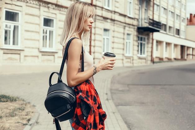 Młoda piękna dziewczyna pije kawę w szklance na ulicy, śmieje się i uśmiecha