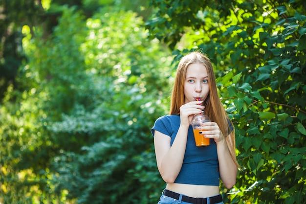 Młoda piękna dziewczyna pije świeżo wyciskanego sok na tle.