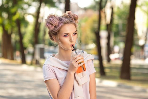 Młoda piękna dziewczyna pije świeży sok od plastikowych takeaway karmowych filiżanek po spaceru outdoors. zdrowy tryb życia. uśmiechnięta szczupła blondynka z różowymi włosami.