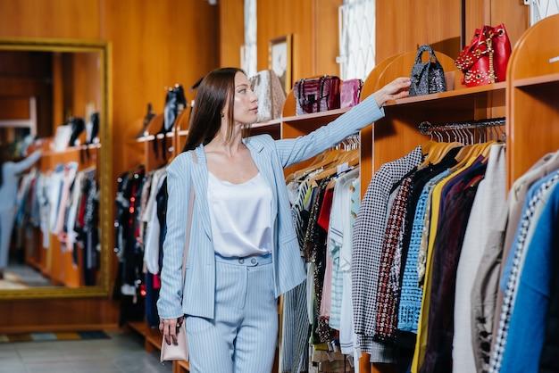 Młoda piękna dziewczyna podnosi ubrania i idzie na zakupy do sklepu.