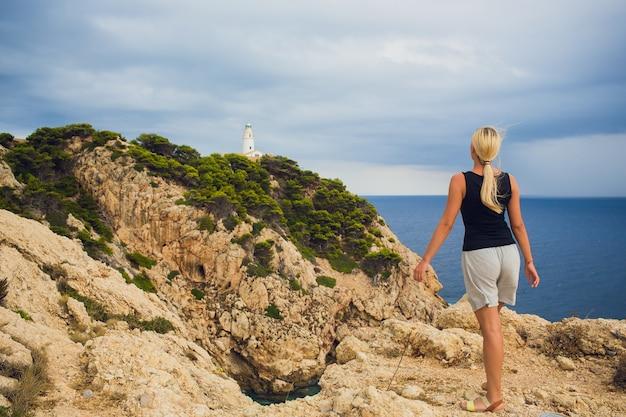 Młoda piękna dziewczyna podróżnik z plecakiem stoi na miasto i latarnię morską na brzegu oceanu.