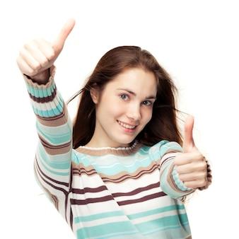 Młoda piękna dziewczyna pokazuje dwa kciuki do góry
