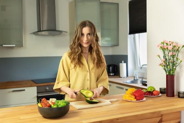Młoda piękna dziewczyna pokrajać dojrzałego avocado. kobieta przygotowuje sałatkę ze świeżych, zdrowych warzyw.