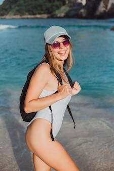 Młoda piękna dziewczyna pozuje na plaży w stroju kąpielowym w czapce i plecaku