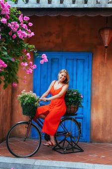 Młoda piękna dziewczyna pozuje siedząc na starym rowerze z kwiatami w koszu na tle starej ściany. dekoracja ogrodu. wietnam
