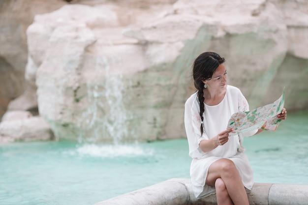 Młoda piękna dziewczyna przy fontannie fontana di trevi z mapą miasta
