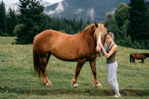 Młoda piękna dziewczyna przytulanie konia w przyrodzie