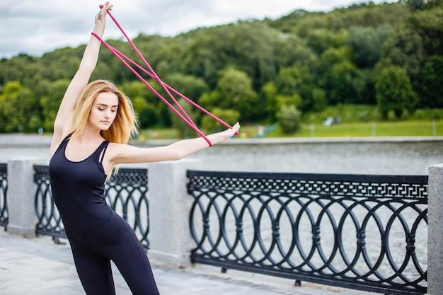 Młoda piękna dziewczyna robi gimnastycznym ćwiczeniom outdoors.