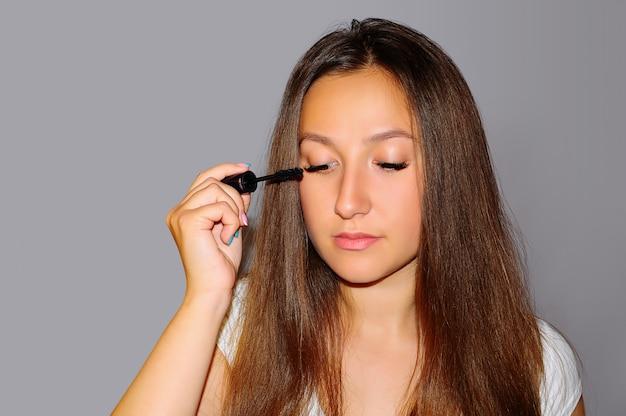Młoda piękna dziewczyna robi makijażu. maluje tusz do rzęs.