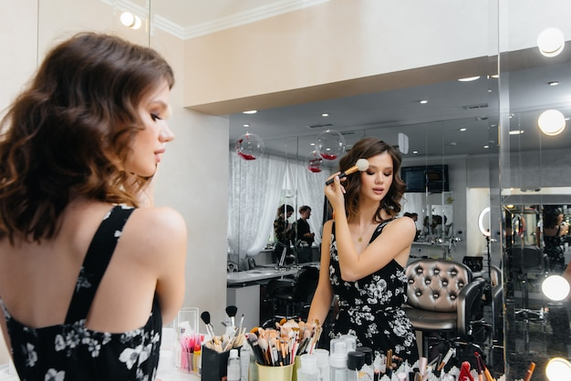 Młoda piękna dziewczyna robi piękny makijaż wieczorowy przed lustrem
