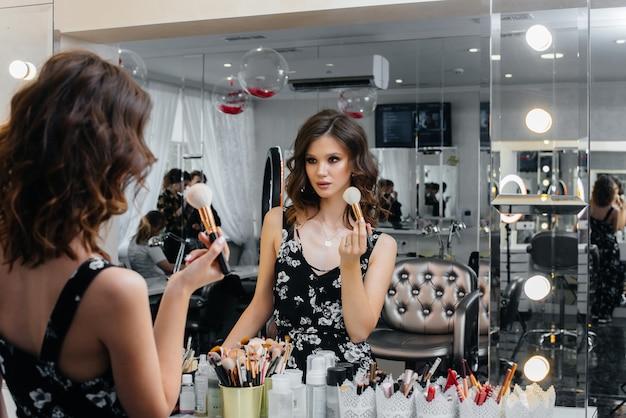 Młoda piękna dziewczyna robi piękny wieczorowy makijaż przed lustrem. moda i uroda.