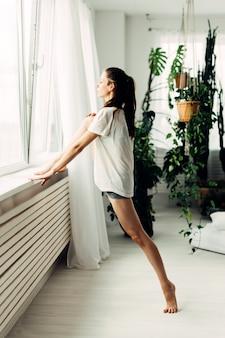 Młoda piękna dziewczyna robi rozgrzewce współczesnej w domu