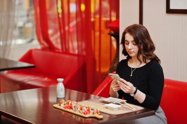 Młoda piękna dziewczyna robi zdjęcie przez telefon sushi w tradycyjnej japońskiej restauracji.
