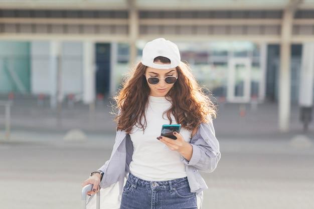 Młoda piękna dziewczyna rozmawia przez telefon w pobliżu dużego przystanku autobusowego z walizką