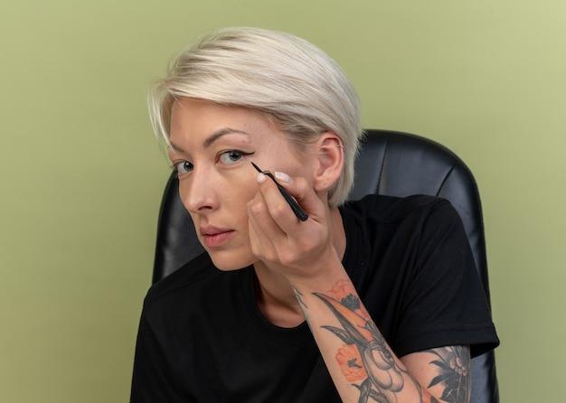 Młoda piękna dziewczyna rysuje strzałkę z eyelinerem odizolowaną na oliwkowozielonej ścianie