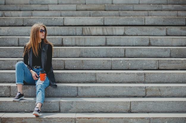 Młoda piękna dziewczyna siedzi na schodach z kawą w okularach.