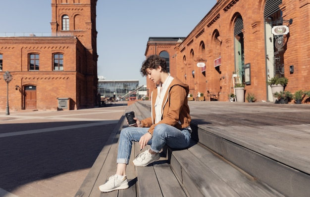 Młoda piękna dziewczyna siedzi na ulicy