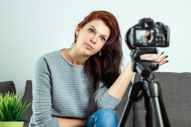 Młoda piękna dziewczyna siedzi przed lustrzanką i nagrywa vlog