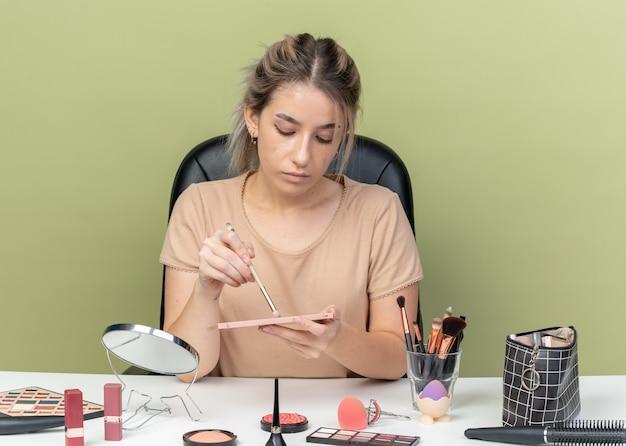 Młoda piękna dziewczyna siedzi przy biurku z narzędziami do makijażu, stosując cień do powiek za pomocą pędzla do makijażu na oliwkowo-zielonym tle