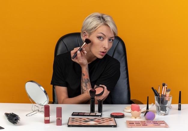 Młoda piękna dziewczyna siedzi przy stole z narzędziami do makijażu, nakładając pudrowy rumieniec za pomocą pędzla do pudru izolowanego na pomarańczowej ścianie