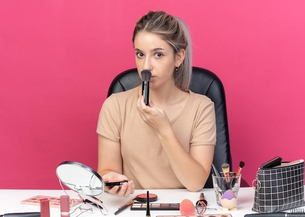 Młoda piękna dziewczyna siedzi przy stole z narzędziami do makijażu, nakładając rumieniec w proszku na różowej ścianie