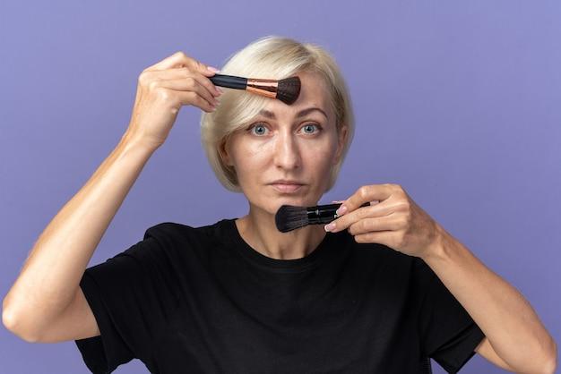 Młoda piękna dziewczyna siedzi przy stole z narzędziami do makijażu, nakładając rumieniec w proszku za pomocą pędzla do pudru izolowanego na niebieskiej ścianie