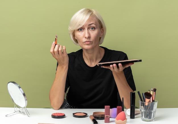 Młoda piękna dziewczyna siedzi przy stole z narzędziami do makijażu, nakładającymi cień do powiek z pędzlem do makijażu odizolowaną na oliwkowozielonej ścianie