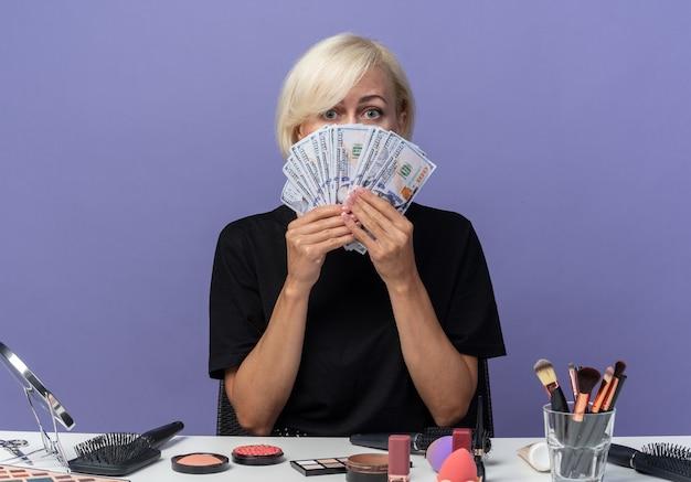 Młoda piękna dziewczyna siedzi przy stole z narzędziami do makijażu pokrytymi twarzą z gotówką odizolowaną na niebieskiej ścianie