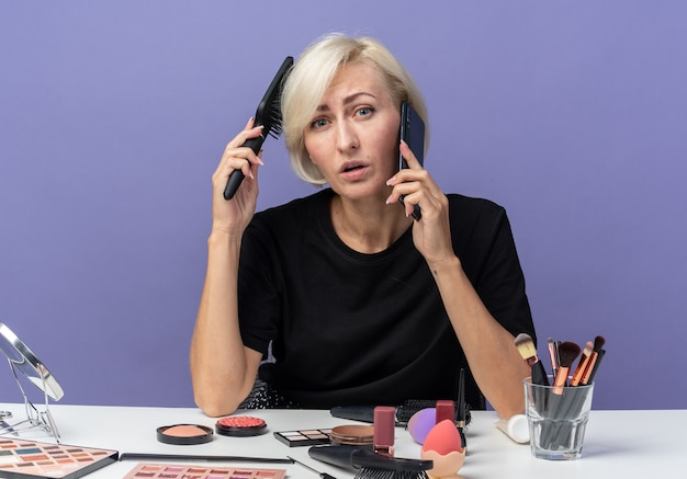 Młoda piękna dziewczyna siedzi przy stole z narzędziami do makijażu, rozmawia przez telefon, czesując włosy izolowane na niebieskiej ścianie